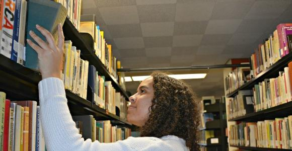 Girl in book stacks.