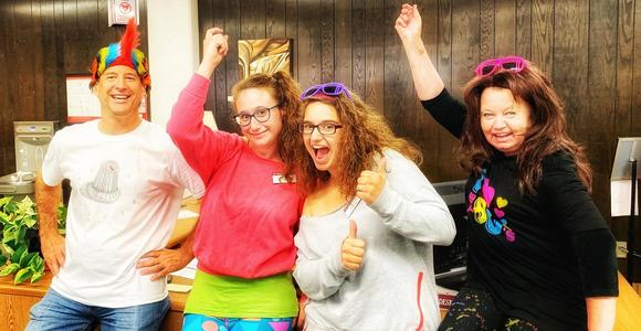 Four Briggs librarians dressed up in 1980s garb being silly.