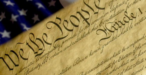 U.S. Constitution with flag in the background
