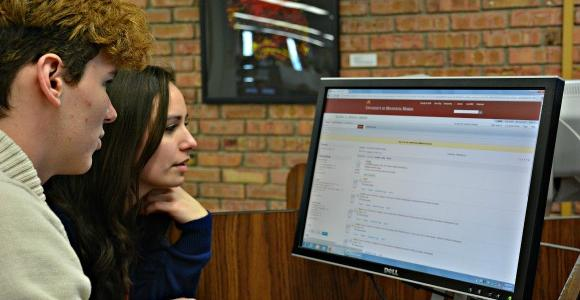 Two students looking at a computer