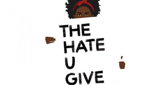 "Black woman holding a sign reading ""The hate u give""."