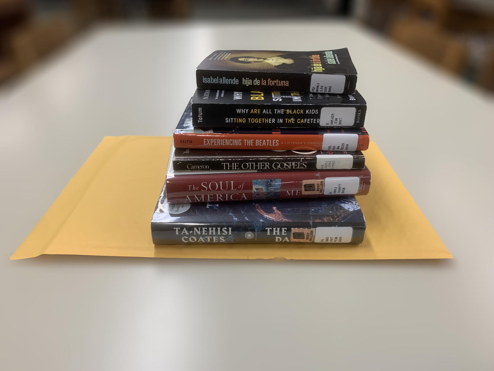 Stack of books on top of a mail envelope.