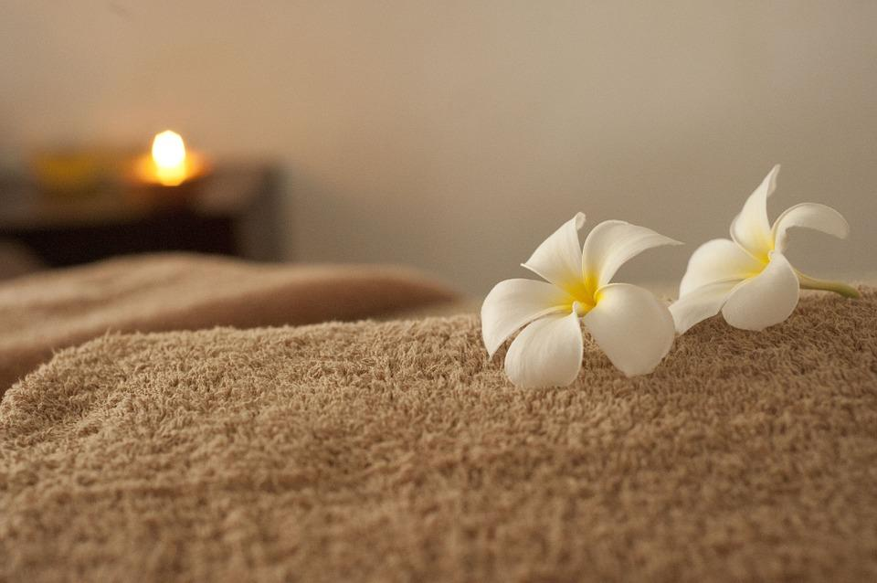 Flowers on a massage bed with a candle