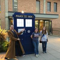 UMM students standing next to the Tardis outside of Briggs Library