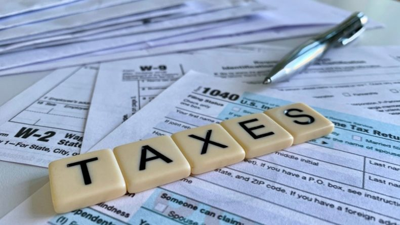 """Tax forms with scrabble-like tiles spelling out """"Taxes""""."""